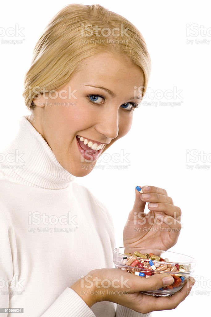 Smiling beautiful young woman  eating colorful pills. royalty-free stock photo