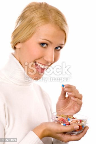 istock Smiling beautiful young woman  eating colorful pills. 91599824