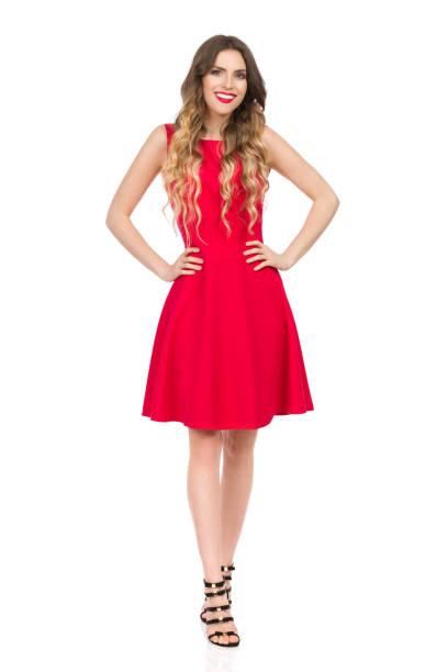 110a65020c Sonriente mujer joven hermosa en Mini vestido rojo es tomados de la mano en  la cadera