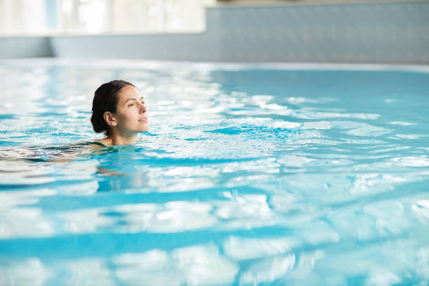 Smiling beautiful young woman swimming in clean water of pool while pending time in fitness club stock photo