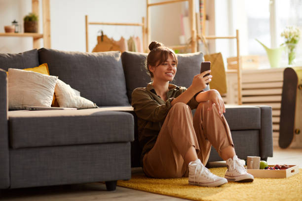 smiling beautiful young woman with hair bun sitting on carpet and reading post on phone while having snack - divano procrastinazione foto e immagini stock