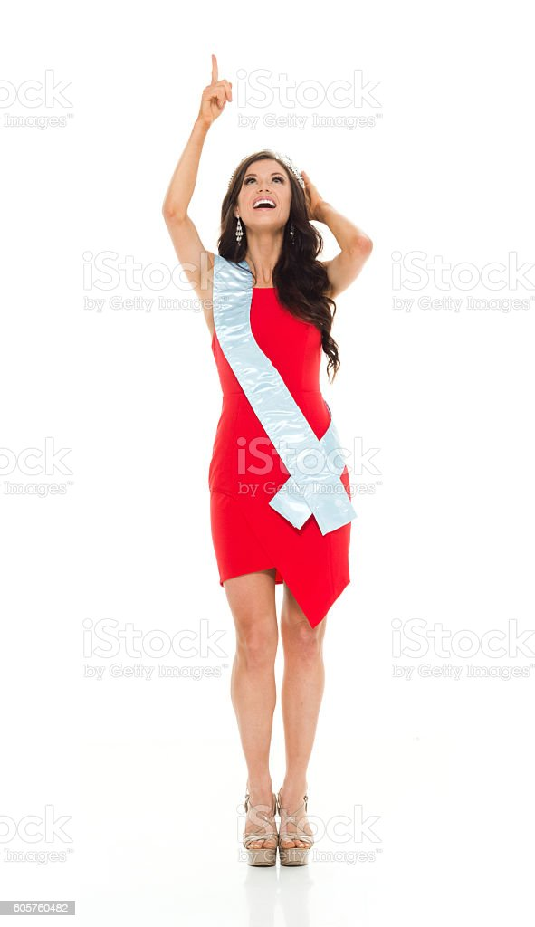 Smiling beauty queen pointing up stock photo