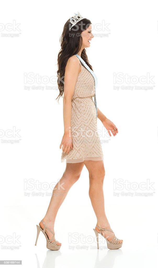 Smiling beauty queen walking stock photo