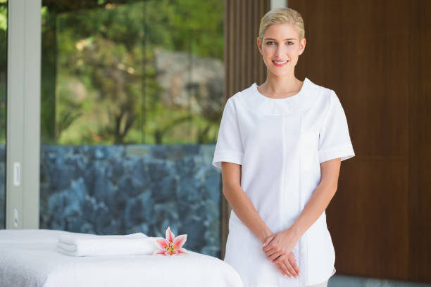 smiling beauty therapist standing beside massage towel - beautician stock photos and pictures