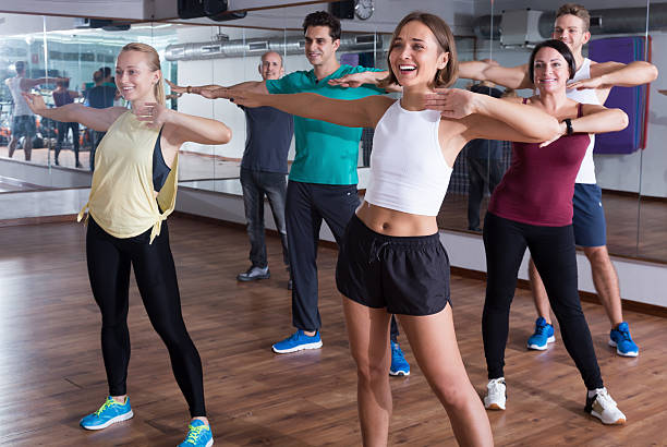 Smiling beginner dancers learning zumba elements stock photo
