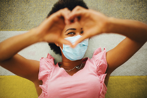 African american young woman lying on the floor, smiling behind protective face mask. Looking at camera through heart shape that she made with her hands.