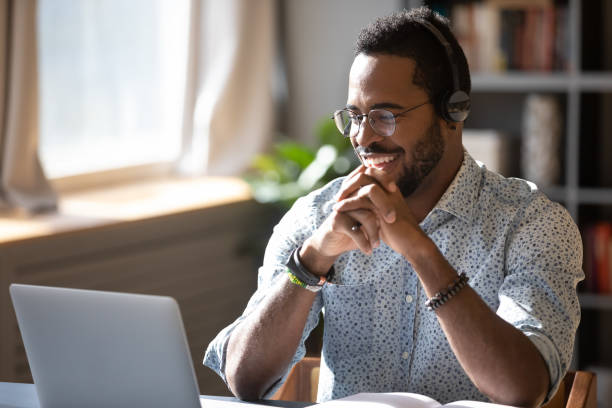 Smiling biracial businessman holding video call with clients partners. Happy millennial african american man in glasses wearing headphones, enjoying watching educational webinar on laptop. Smiling young mixed race businessman holding video call with clients partners. showing stock pictures, royalty-free photos & images