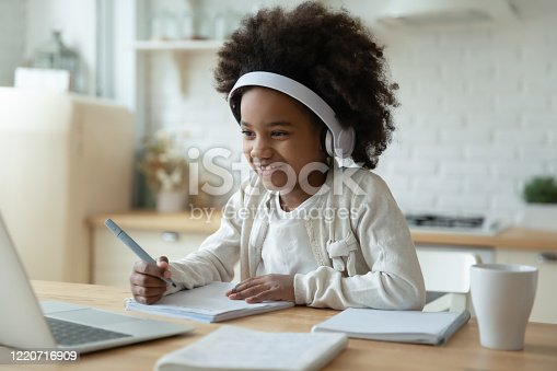 Smiling small African American girl in headphones watch video lesson on computer in kitchen, happy little biracial child in earphones have online web class using laptop at home, homeschooling concept