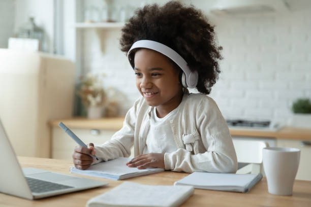 Smiling biracial girl watch video on laptop at home stock photo