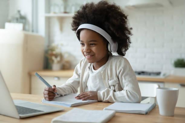 lächelnde biracial mädchen sehen video auf laptop zu hause - homeschooling stock-fotos und bilder