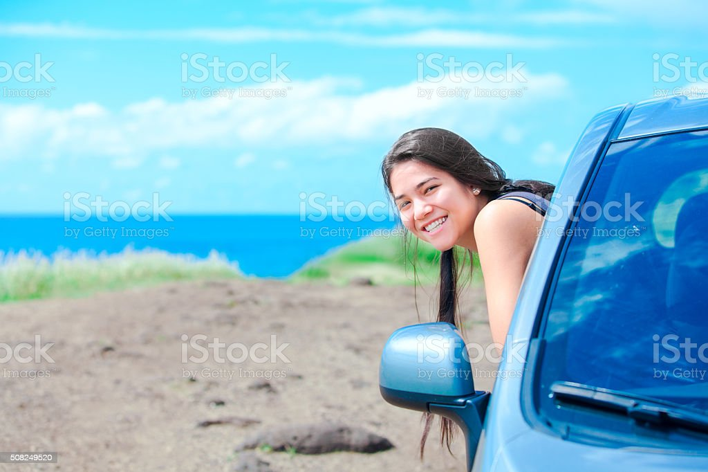Smiling biracial teen girl leaning out car door by ocean royalty-free stock photo