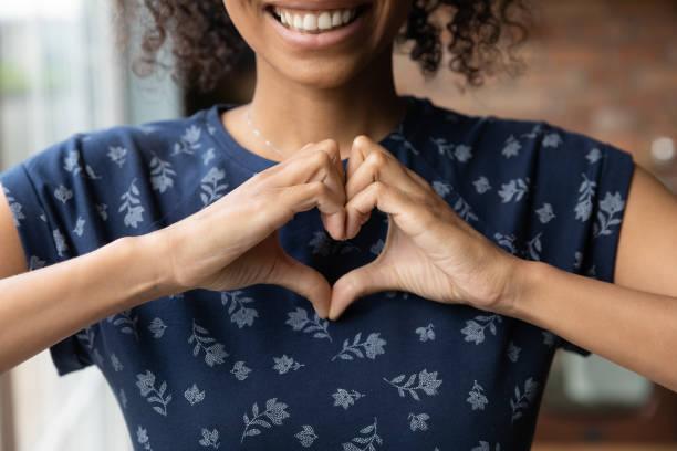 Smiling biracial woman show heart hand gesture stock photo