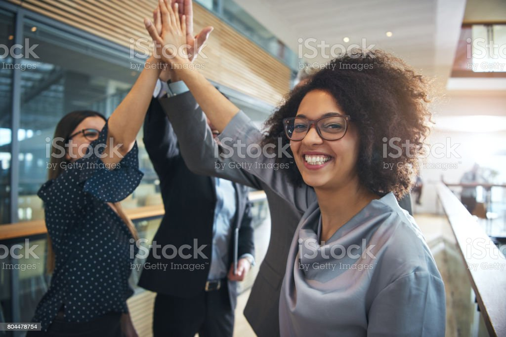 Smiling black businesswoman giving high five to ofiice team - foto stock