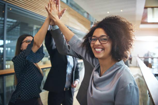 sonriendo a empresaria negro dando alta cinco al equipo de ofiice - high five fotografías e imágenes de stock