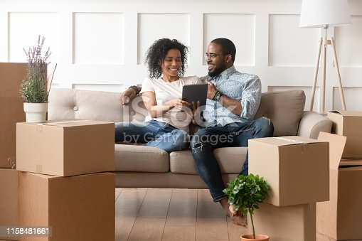 istock Smiling black couple use digital tablet on moving day 1158481661