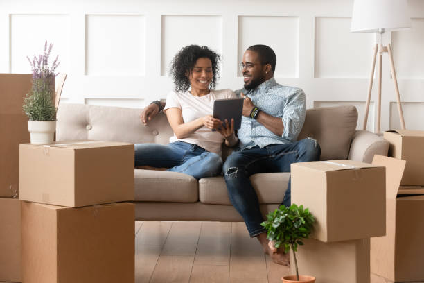 smiling black couple use digital tablet on moving day - furniture shopping stock photos and pictures
