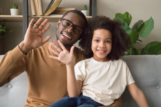 Smiling black dad and daughter wave talking on webcam Happy african American dad and daughter sit on couch wave talking on webcam having skype conversation, smiling black father and girl child blogger say hello to viewers record youtube vlog or blog young girls on webcam stock pictures, royalty-free photos & images