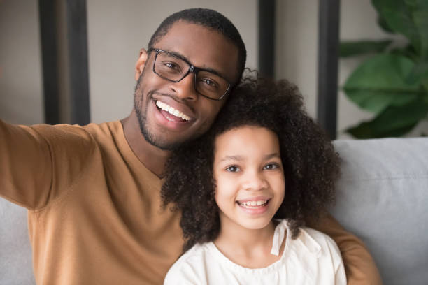 Smiling black father and child taking selfie looking at camera Smiling black father and child daughter taking selfie together looking at camera, head shot portrait of happy african family dad with kid embracing posing making photo recording video, phone cam view young girls on webcam stock pictures, royalty-free photos & images