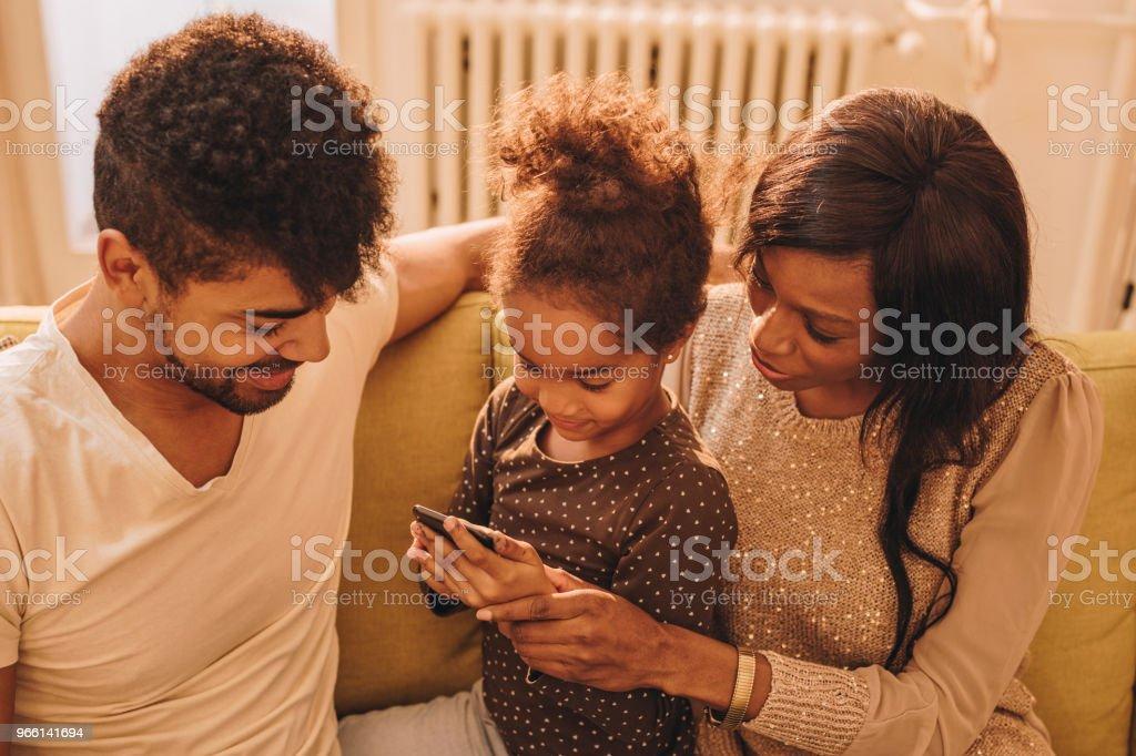 Lächelnde schwarze Mädchen und ihren Eltern Spaß beim mit Smartphone. - Lizenzfrei Afrikanischer Abstammung Stock-Foto