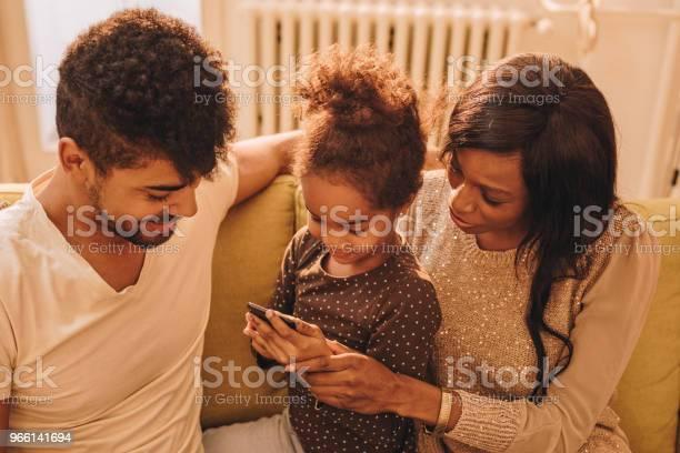 Lächelnde Schwarze Mädchen Und Ihren Eltern Spaß Beim Mit Smartphone Stockfoto und mehr Bilder von Afrikanischer Abstammung