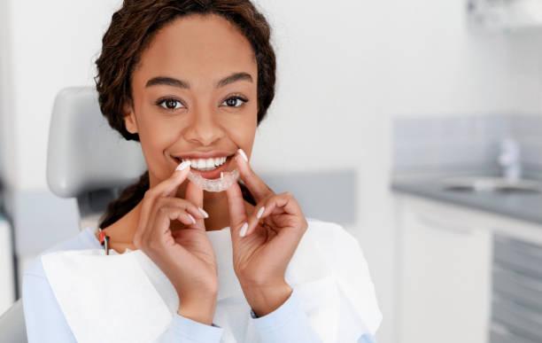 Smiling black girl holding invisible aligner, modern teeth trainer stock photo