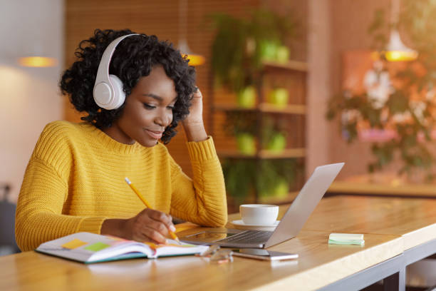 Smiling black girl with headset studying online, using laptop stock photo