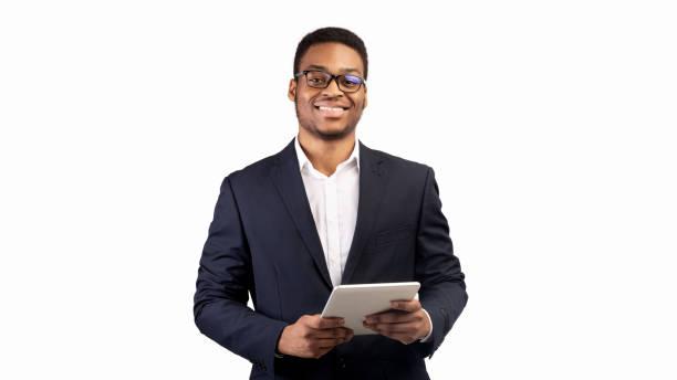 lächelnder schwarzer kerl steht mit tablet im studio - weißer hintergrund stock-fotos und bilder