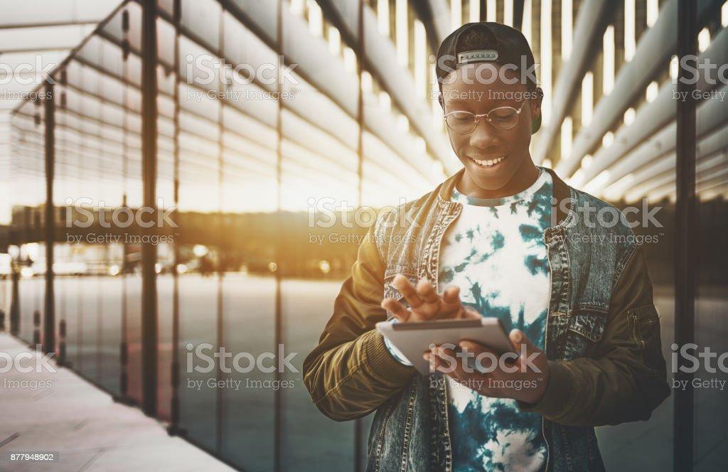 Smiling black guy using tablet pc on street stock photo