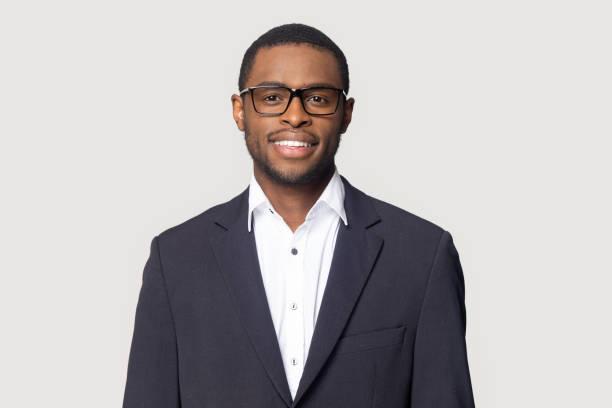 hombre negro sonriente en traje posando en el fondo del estudio - black people fotografías e imágenes de stock
