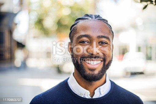An attractive young black man in business attire outdoors.