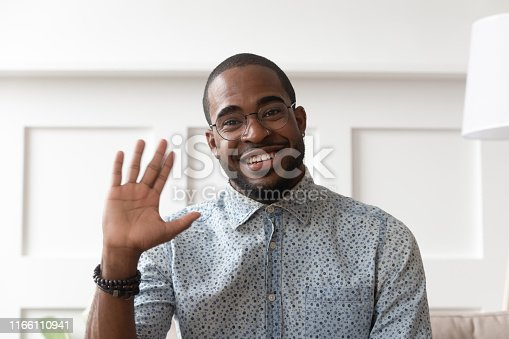 Smiling african American millennial man in glasses look at camera waving saying hello talking on video call, happy black male vlogger in spectacles greeting with subscribers shooting video blog