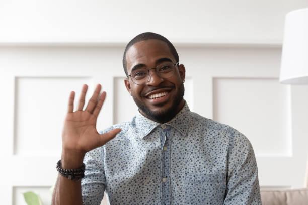 smiling black man waving talking on video call - sventolare la mano foto e immagini stock