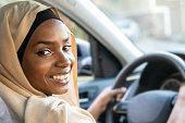 Smiling black muslim woman driving her vehicle