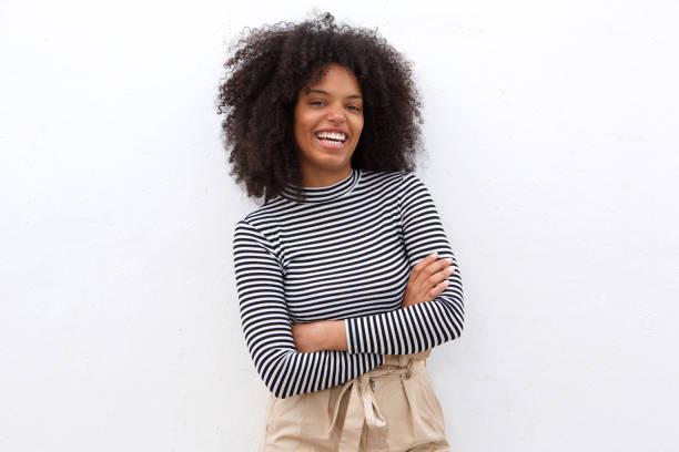 lächelnde schwarze Frau in gestreiften Hemd mit verschränkten Armen – Foto