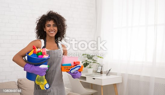 istock Smiling black woman posing with cleaning supplies 1080849746