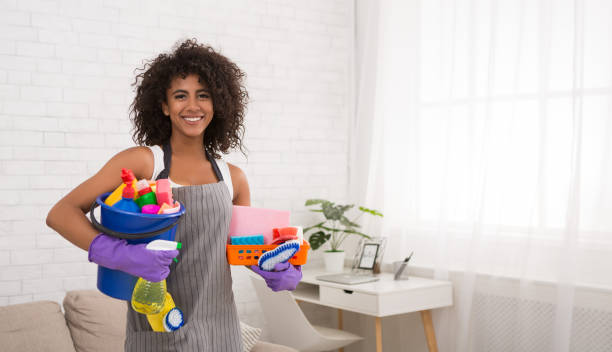 lachende zwarte vrouw poseren met schoonmaakproducten - vrouw schoonmaken stockfoto's en -beelden