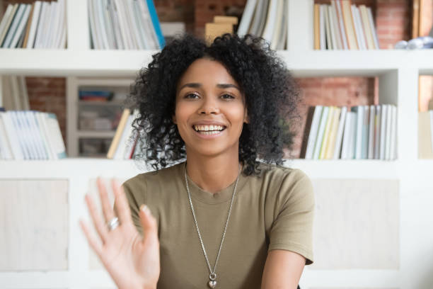 smiling black woman waving talking on webcam - webcam stock pictures, royalty-free photos & images