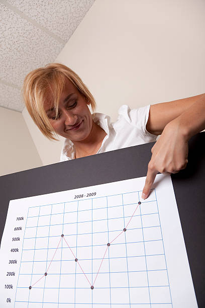 Smiling blond businesswoman with chart stock photo