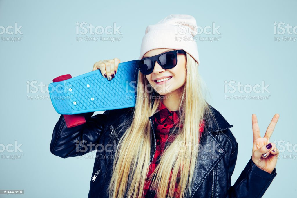 Smiling blond teenager girl in black sunglasses and pink hat stock photo