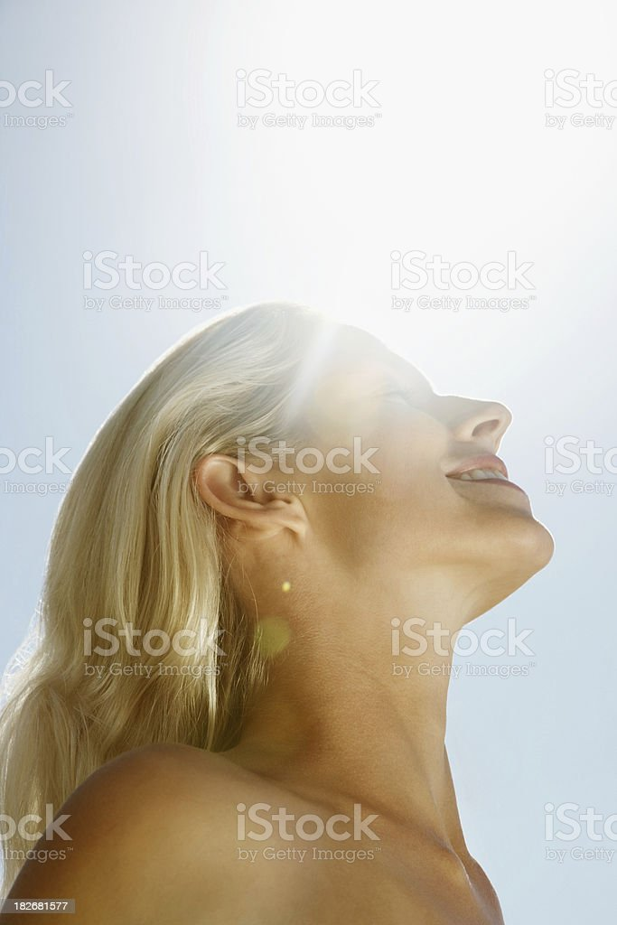 Smiling blond woman against the sunny sky royalty-free stock photo