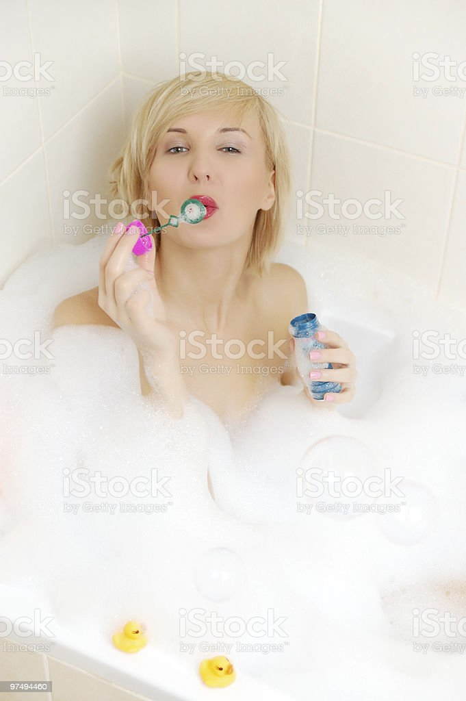 Smiling blond woman lying in bubble bath royalty-free stock photo