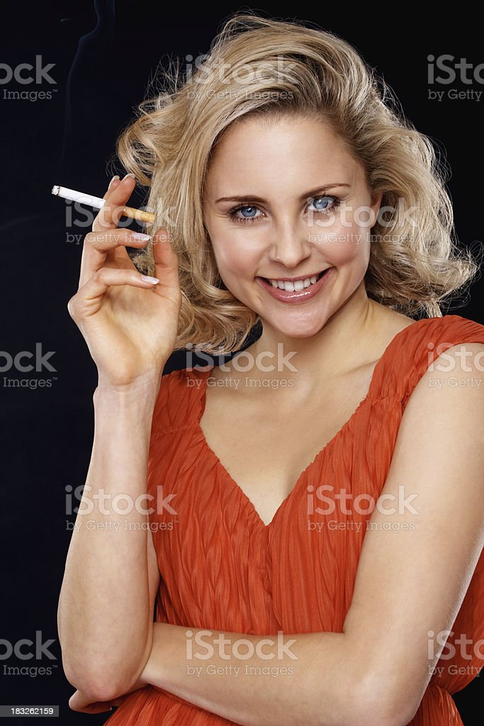 Smiling blond woman smoking a cigarette stock photo