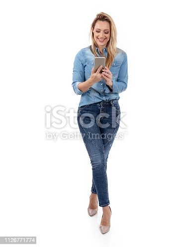 istock Smiling blond woman texting on the phone 1126771774