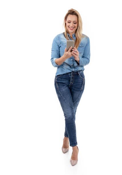 lächelnden blonden frau sms auf dem handy - damenschuhe 44 stock-fotos und bilder