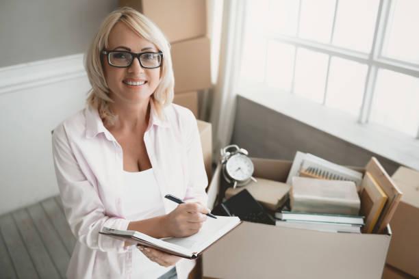 lächelnden blonden frau mit brille mit notebook. - umzug checkliste stock-fotos und bilder
