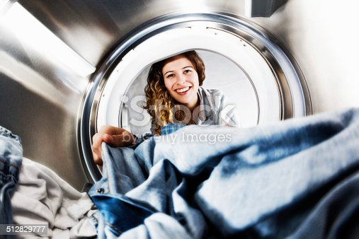 In an unusual view from inside the washing machine drum, a smiling and pretty blonde loads - or unloads - laundry.