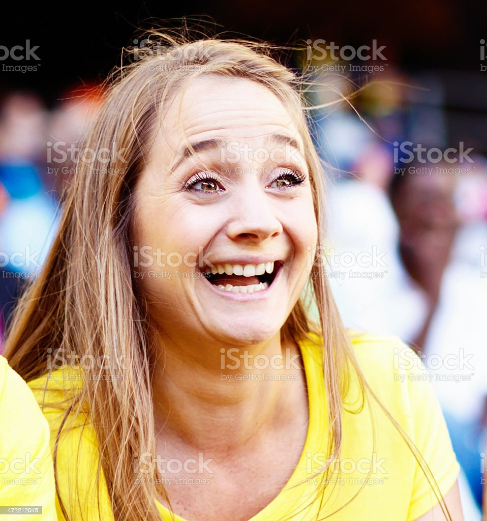 Smiling blonde beauty supporting soccer team at match stock photo