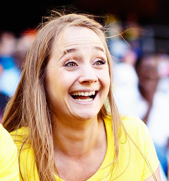 lächelnde blonde schönheit, die unterstützung der fußball team im spiel - spielerfrauen stock-fotos und bilder