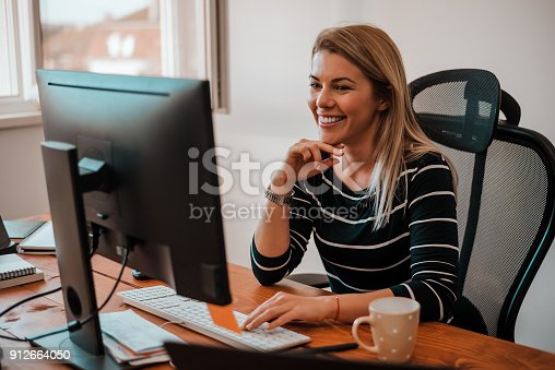 istock Smiling blonde business woman working at office desk. 912664050