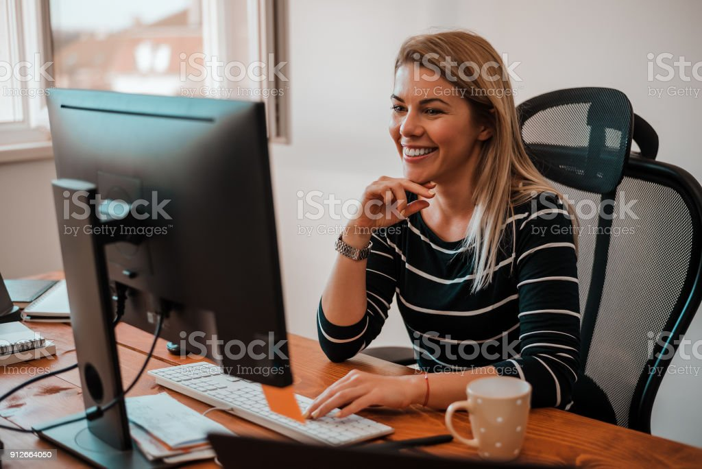 Smiling blonde business woman working at office desk. stock photo